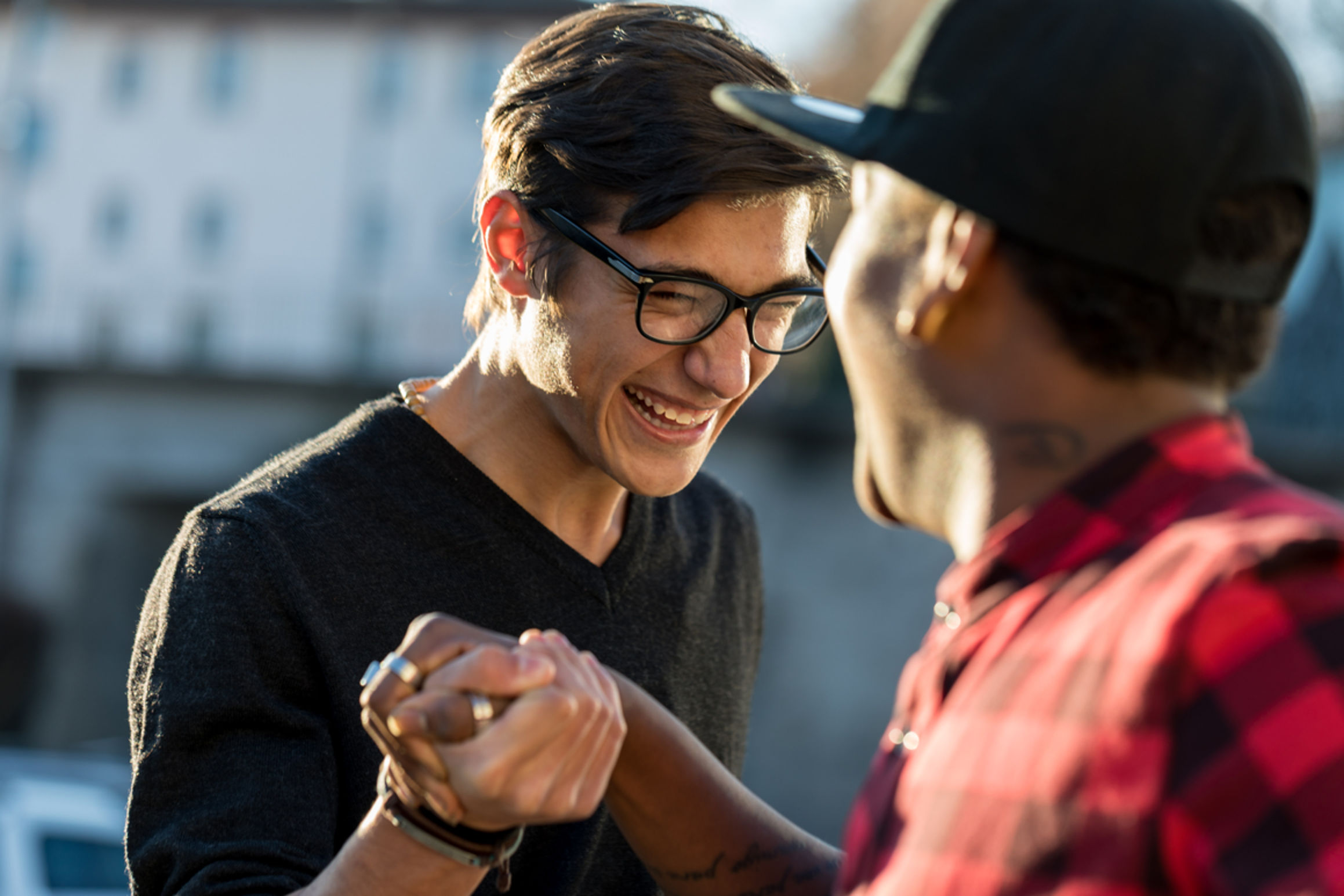 two guys greeting each other smiling, hands grasped